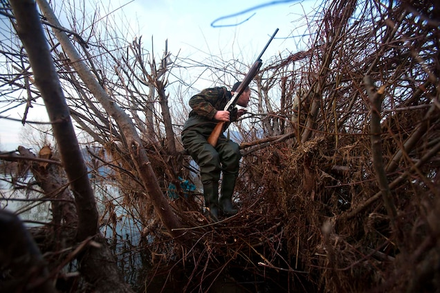 A hunter peers from a tree stand on Lake Shkoder in Albania. PHOTOGRAPH BY DAVID GUTTENFELDER, AP