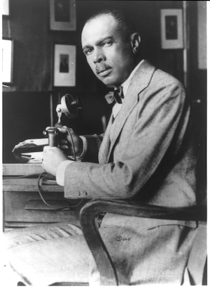 James Weldon Johnson in a suit sitting by a telephone looking into camera