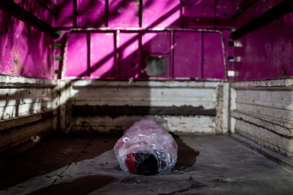 The body of a man who died from COVID-19 lies cocooned in plastic wrap.