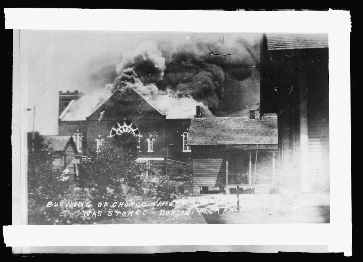 a church on fire with smoke billowing from the top
