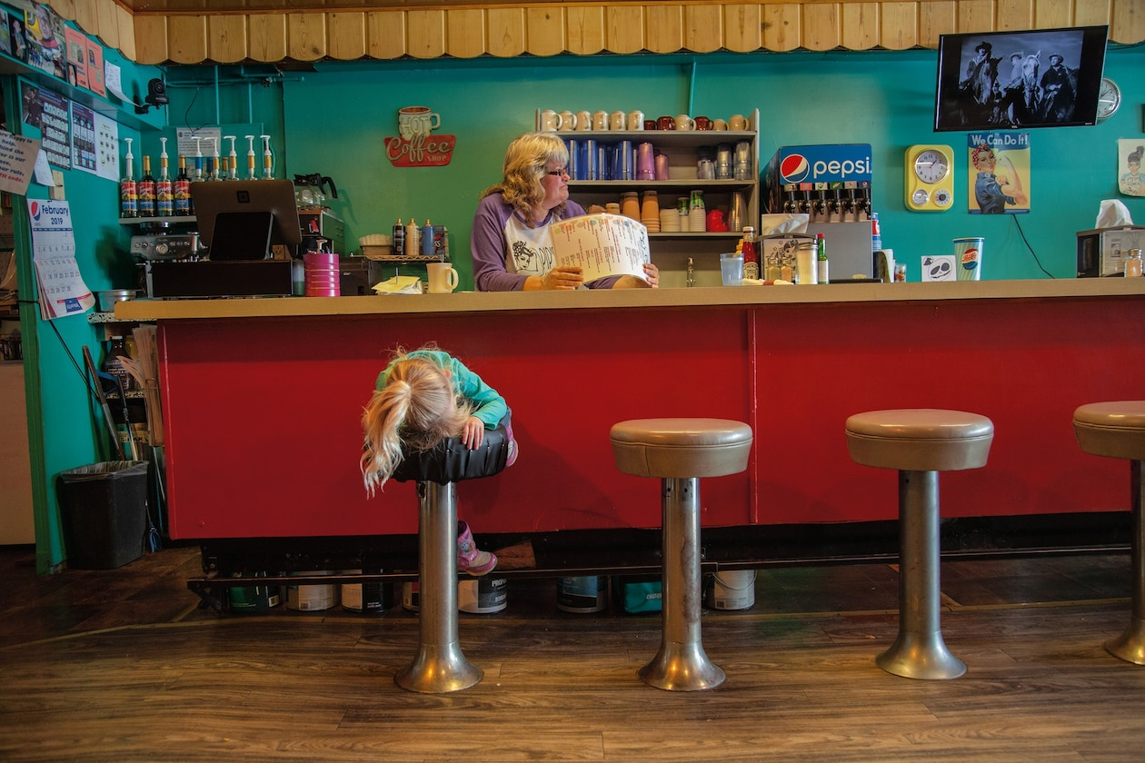 a young girl on the bar stool of a diner