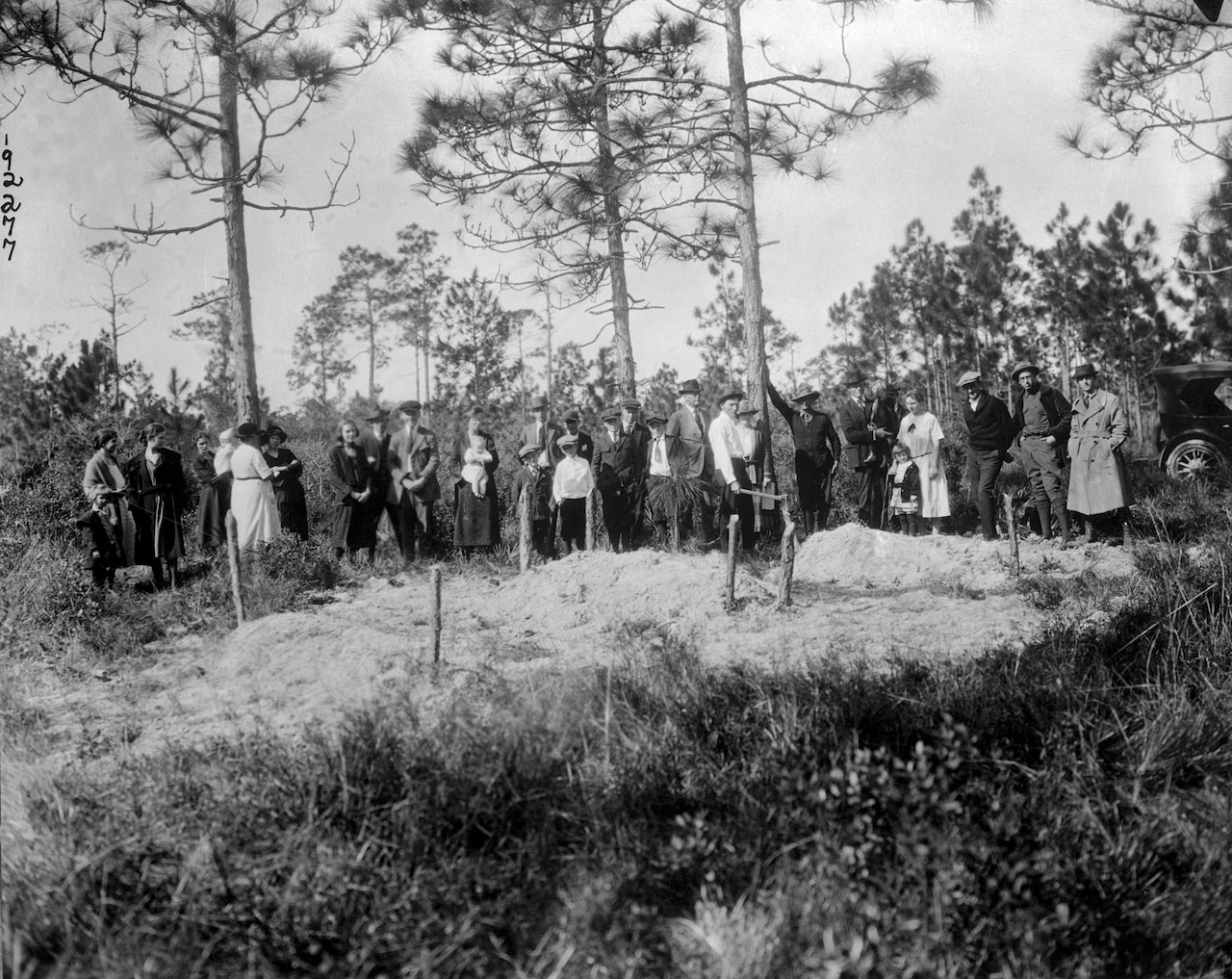 a grave site with a crowd of white people standing around it