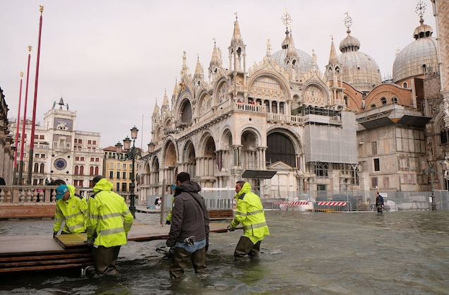 Workers prepare a temporary catwalk in a flooded St. Mark's Square.