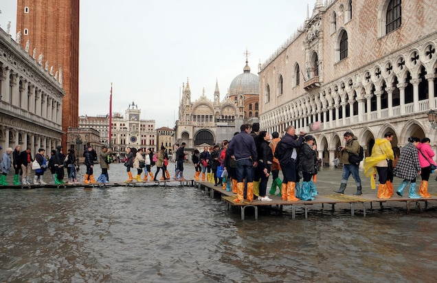 People walk on a catwalk in a flooded St. Mark's Square during a period of seasonal high water in Venice, Italy, on October 29, 2018.