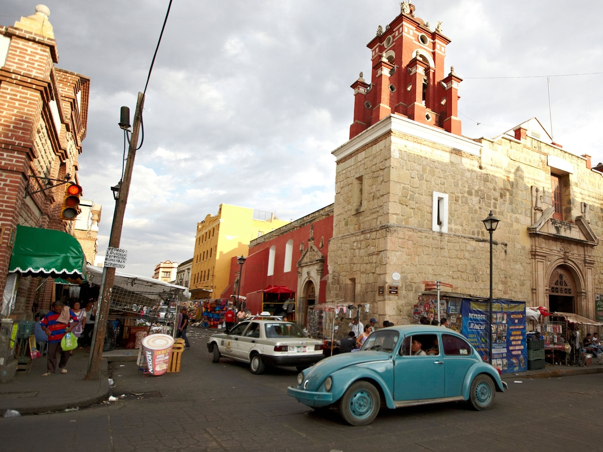 a person driving a blue car on a street in Mexico