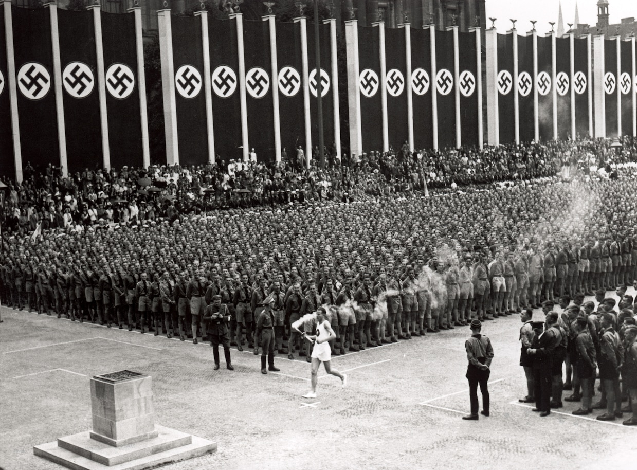 a runner delivers the Olympic torch in the 1936 Olympic Games in Berlin