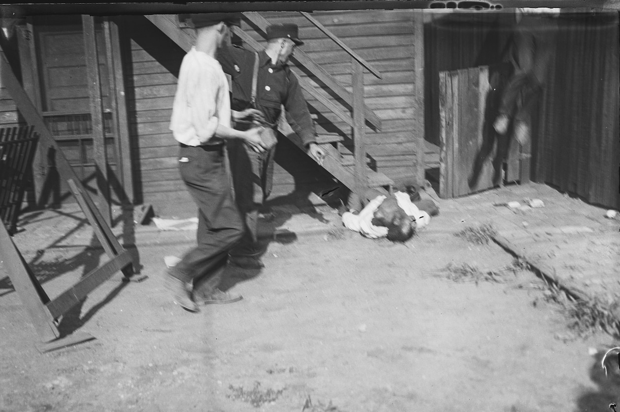 Picture two white men beating a black man with stones