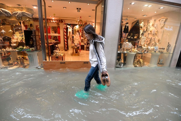A woman walks in a flooded Venetian street. According to city officials, about 75 percent of the lagoon city was inundated in the 2018 floods.