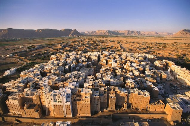"""<p>In the heart of Wadi Hadramaut, the 16th-century <a href=""""https://www.nationalgeographic.com/travel/article/shibam-mud-skyscraper-yemen"""" target=""""_blank"""">Walled City of Shibam</a> is the oldest standing metropolis in the world to use vertical construction. In the 1930's, British explorer Freya Stark dubbed the mud skyscraper city """"the Manhattan of the desert"""".</p> <p>In 2015, Shibam was added to the list of World Heritage in Danger due to ongoing civil war. """"In addition to causing terrible human suffering, these attacks are destroying Yemen's unique cultural heritage, which is the repository of people's identity, history and memory and an exceptional testimony to the achievements of the Islamic Civilization,"""" Director-General Irina Bokova said in a <a href=""""http://whc.unesco.org/en/news/1278/"""" target=""""_blank"""">press release</a>.</p>"""