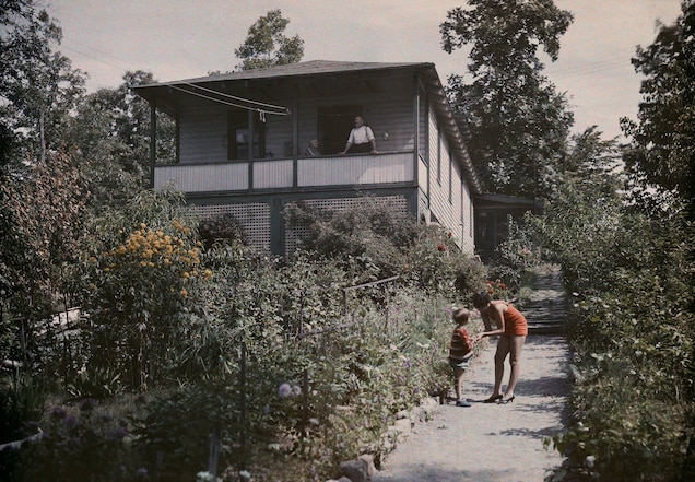<p>A woman speaks with a child at a summer cottage on Lake Hopatcong, New Jersey. Though many women traveled extensively in the 1920s, solo trips were more difficult to undertake, as married women were only issued passports in their husband's name.</p>