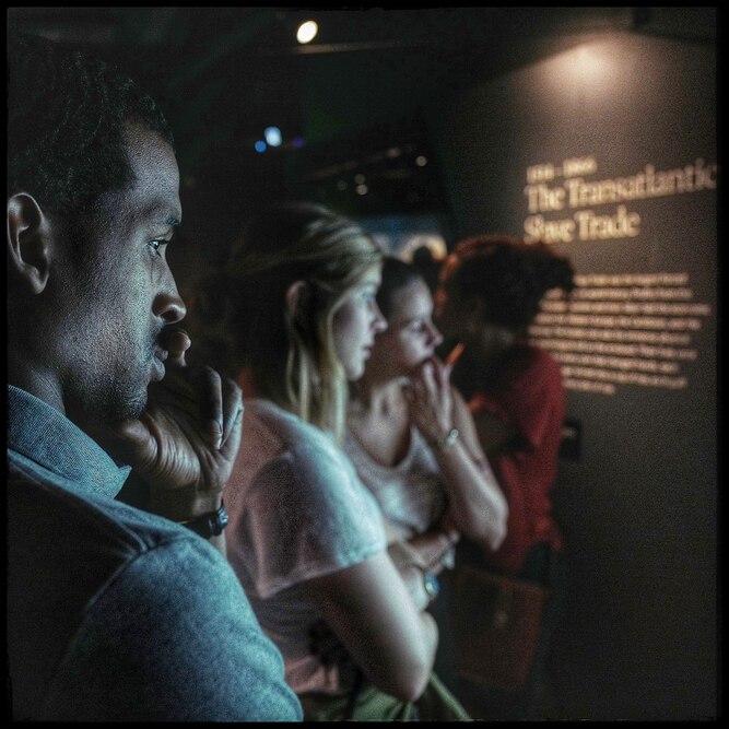 一个人沉思地读了一本关于跨大西洋奴隶贸易的展览。