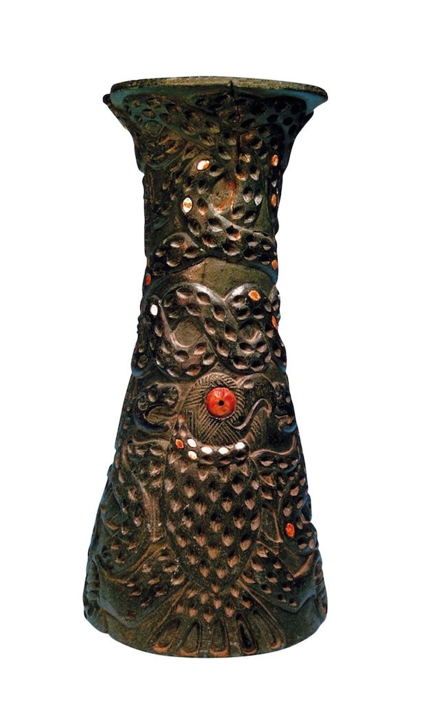 An eagle carved onto a dark vase