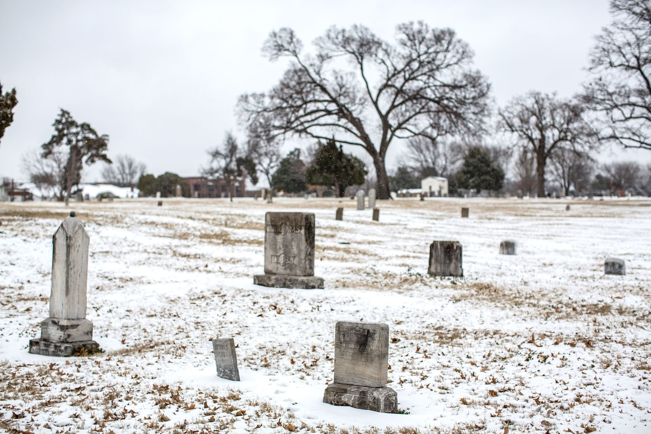 a grave yard with a layer of snow on top