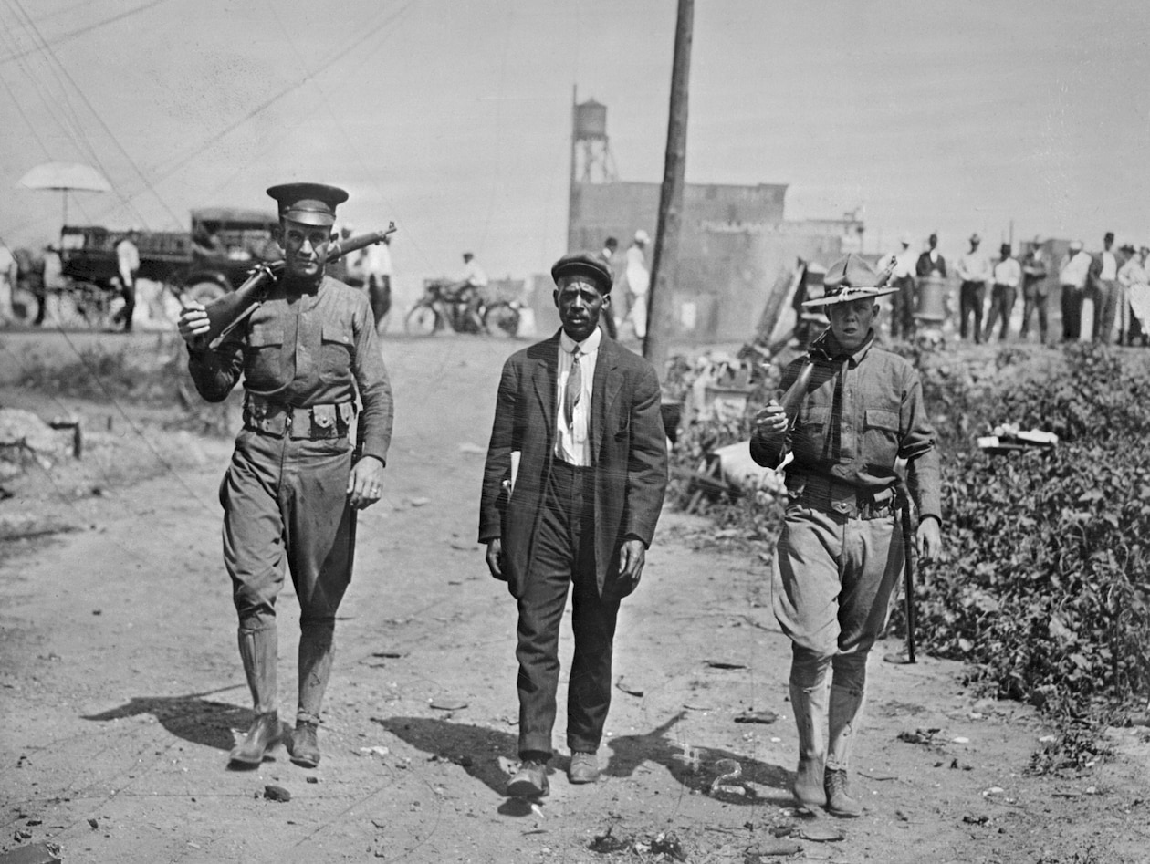 two national guards walking on either side of an African American man