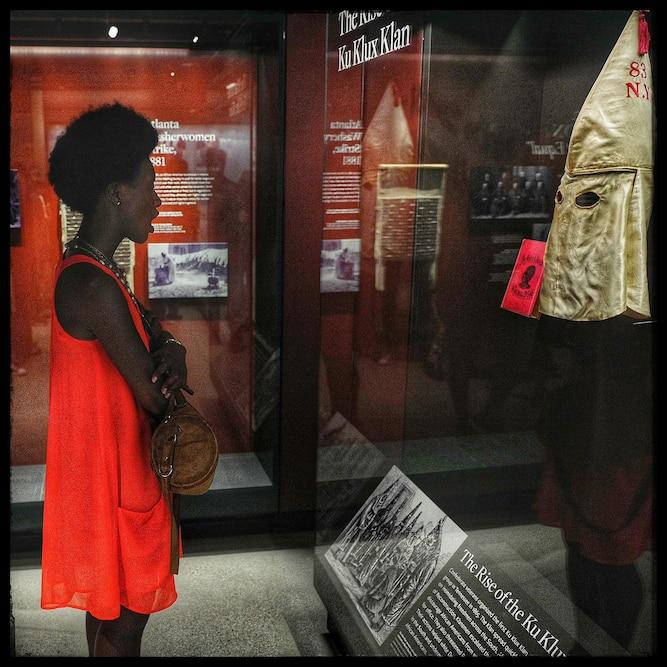 一名妇女凝视着陈列在博物馆的Ku Klux Klan成员的面具后喘息。