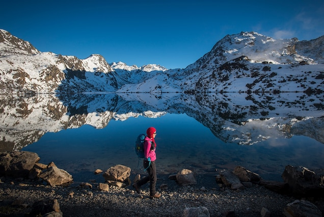 a woman walking past the holy lake of Gosainkund in the Langtang region of Nepal