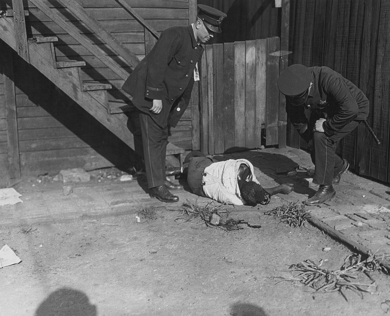 two police officers examining a dead African American man who was recently beaten up