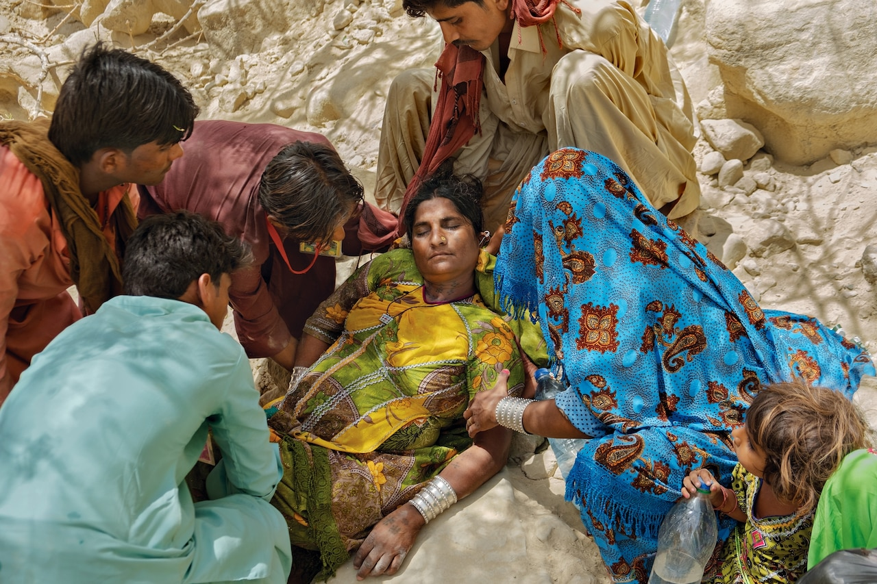 Picture of woman with eyes closed on the ground assisted by three men and one woman