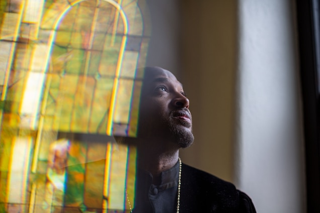 Rev. Robert Turner with a reflection of a stained glass window on the left side
