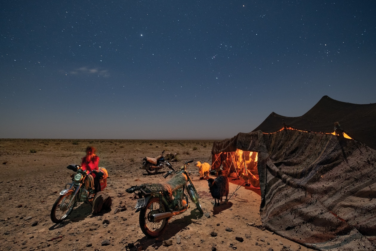 Picture of man on motorbike by campsite in the desert at night