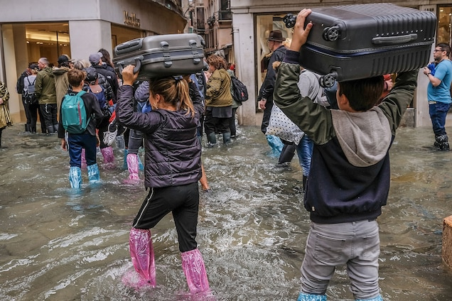 People carry their luggage over their heads to keep it as dry as possible.