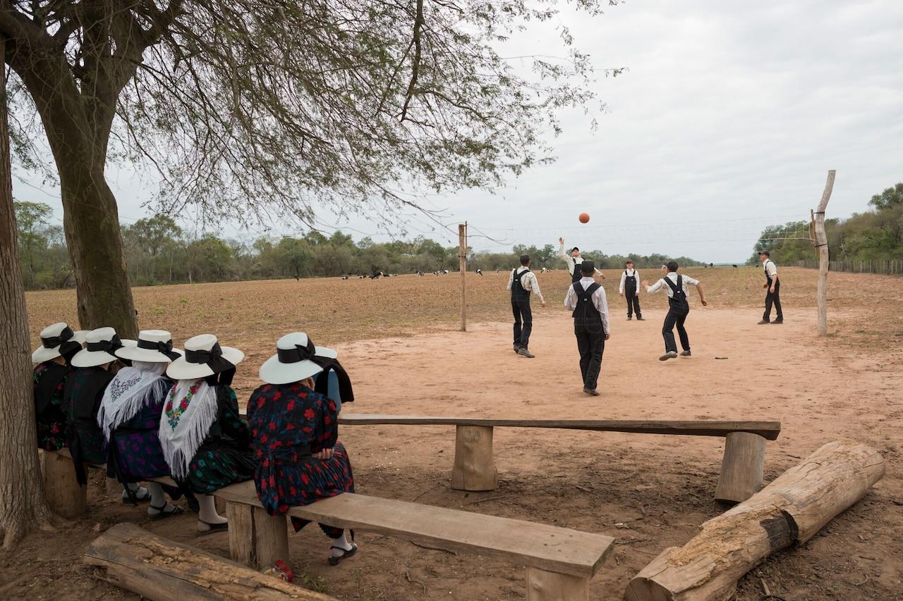 Los hombres jóvenes menonitas de entre 15 y 21 años juegan voleibol durante una salida dominical mientras las mujeres jóvenes los miran.  Colonia El Palmar, Bolivia.  2013