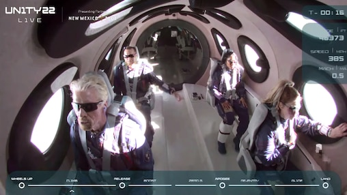 Virgin Galactic's Richard Branson and other passengers wait for the VSS Unity, Virgin Galactic's sub-orbital rocket-powered space plane, to be released from the mothership.