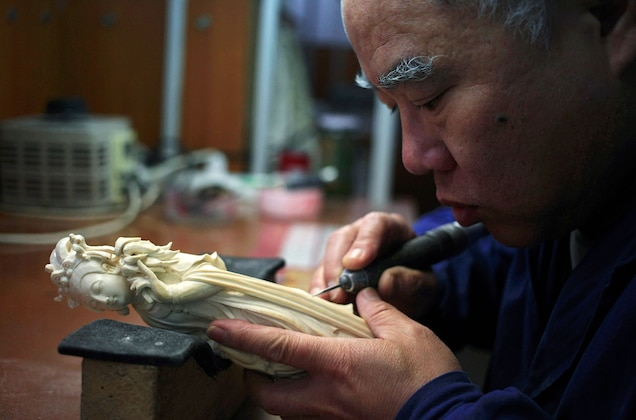 An artist carves an ivory sculpture in the Beijing Ivory Carving Factory. The government has not said what its plans are for ivory workshops once the ban on the ivory trade goes into effect. Photograph by How Hwee Young, EPA