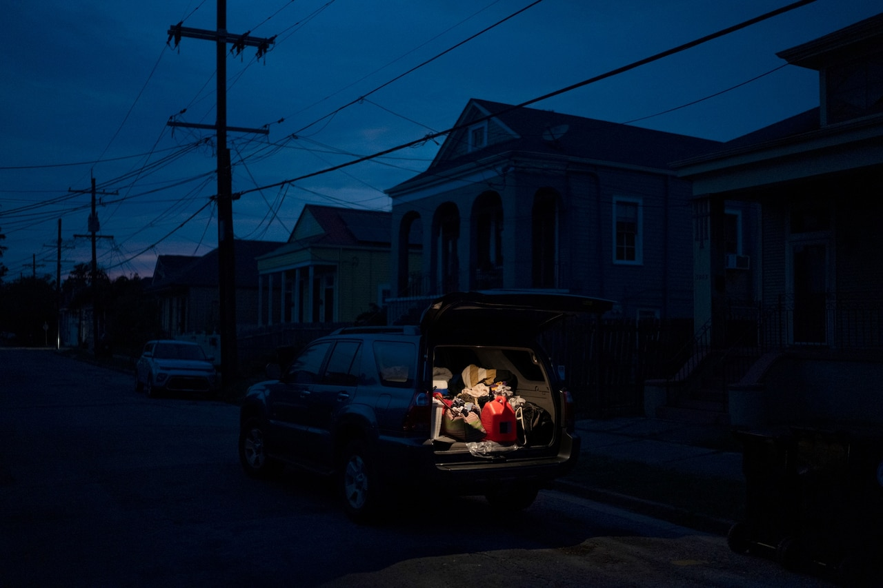 a small light illuminates the interior of a car in a neighborhood left pitch black from power outages